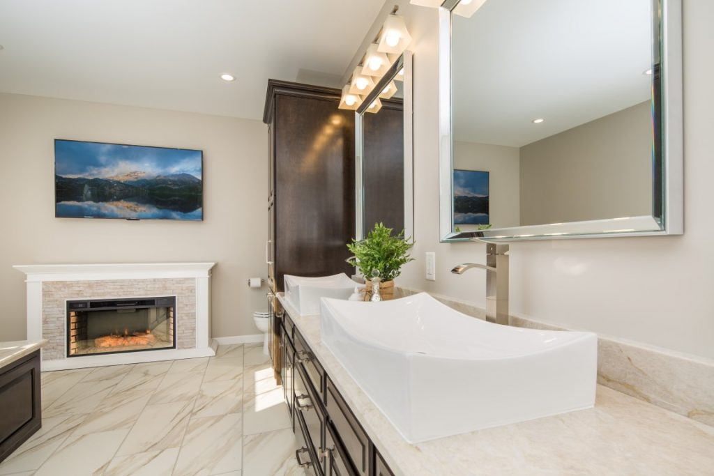 Master bath remodel features electric fireplace, big screen TV, and custom birch cabinets.