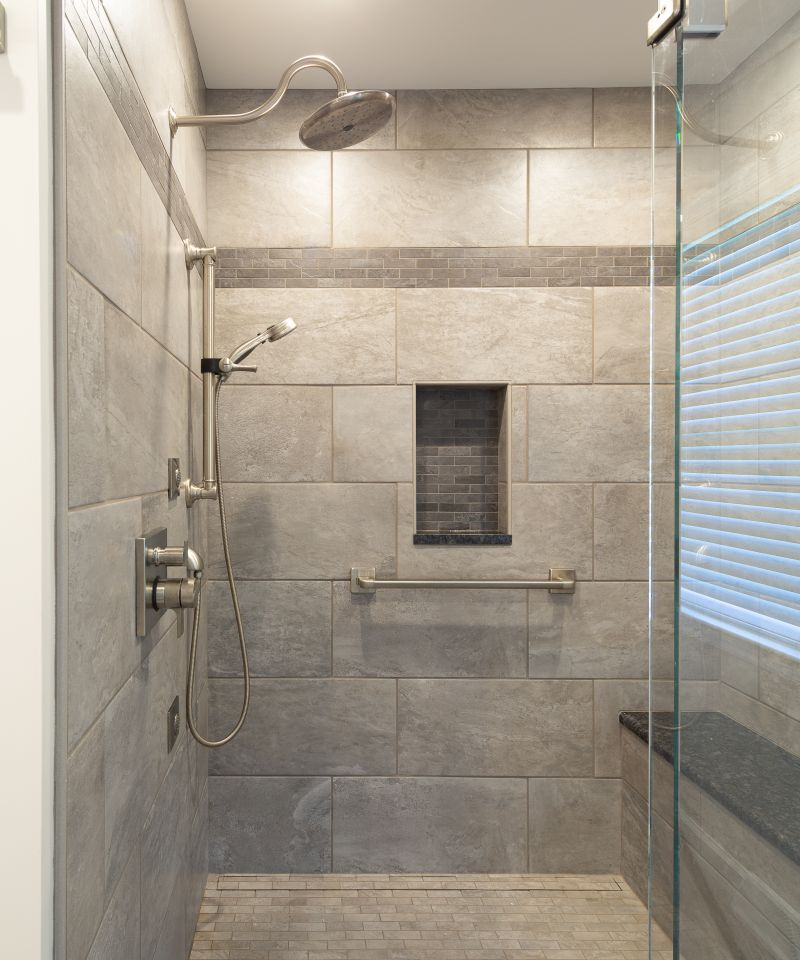 Inside tile shower with glass door open.